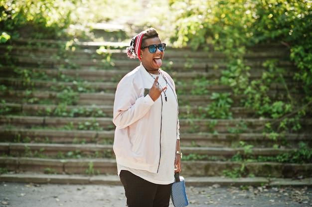 Cara de homem árabe elegante hipster de chapéu e óculos de sol colocados ao ar livre na rua, mostra tonque e dois dedos.