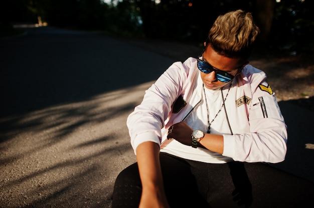 Cara de homem árabe hipster elegante em óculos de sol posou ao ar livre na rua ao pôr do sol, sentado na estrada nas sombras.