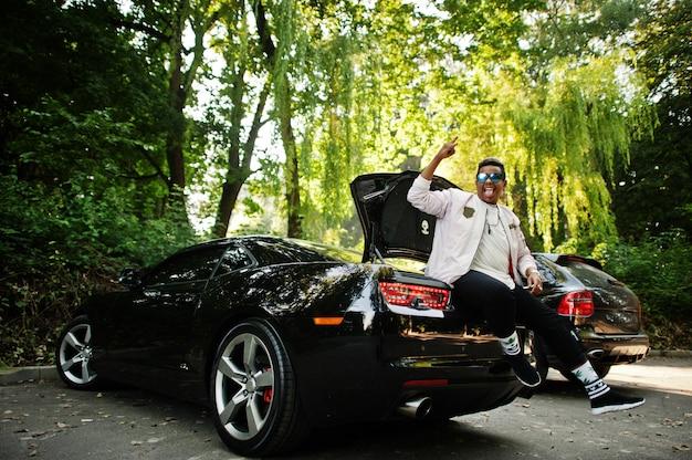 Cara de homem árabe hipster elegante em óculos de sol posou ao ar livre na rua e sentado no porta-malas seu carro preto do músculo. homem negro rico.