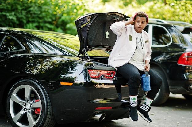 Cara de homem árabe hipster elegante no chapéu posou ao ar livre na rua e sentado no porta-malas seu carro preto do músculo.