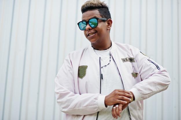Cara de homem árabe hipster elegante posou ao ar livre na rua. cantor de rap estilo contra a parede de aço.