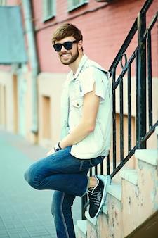 Cara de homem bonito hipster sorridente engraçado em pano elegante de verão na rua em óculos de sol