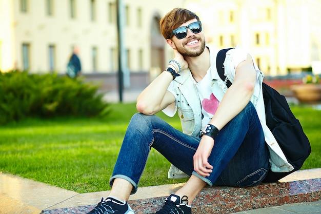 Cara de homem bonito hipster sorridente engraçado em pano elegante de verão na rua sentado na grama do parque