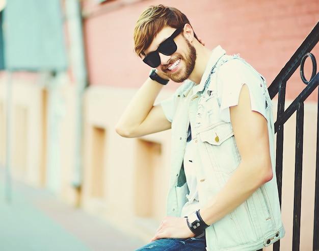Cara de homem bonito hipster sorridente engraçado em roupas de verão elegante na rua em óculos de sol