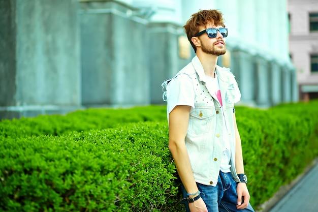 Cara de homem bonito hipster sorridente engraçado em roupas de verão elegante na rua posando perto da cidade verde