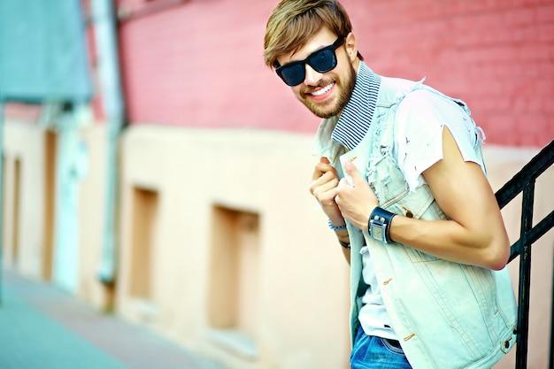 Cara de homem bonito hipster sorridente engraçado em roupas de verão elegante posando na rua