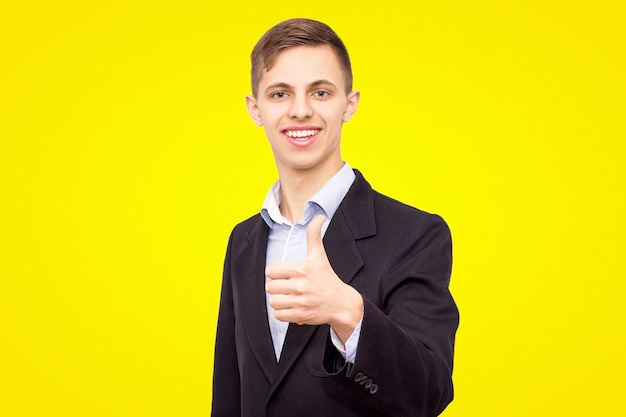Cara de jaqueta e camisa azul mostra um dedo para cima isolado em um fundo amarelo