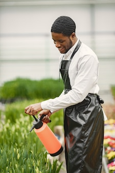 Cara de jardineiro africano. jardineiro com regador. canteiros de flores.
