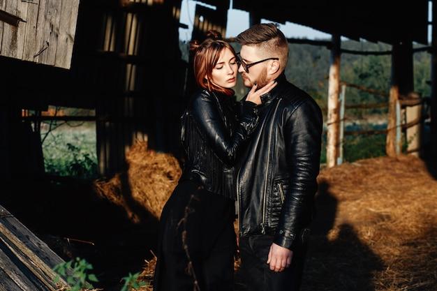 Cara de moda com sua namorada ficar em jaquetas de couro preto e olhar uns aos outros