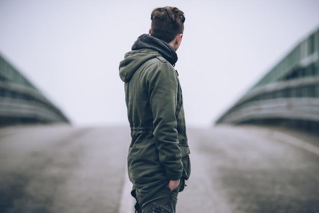 Cara de moda jovem de pé no centro de uma estrada vazia - conceito de estilo de vida de liberdade de viagem - viajante menino no olhar filtrado de humor escuro