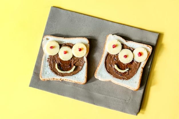 Cara de monstro engraçado no halloween sanduíche torrar pão com manteiga de amendoim, queijo em fundo amarelo guardanapo close-up. crianças criança doce sobremesa café da manhã almoço comida.