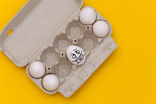 Cara de ovo em máscara médica e bandeja de ovos em fundo amarelo. covid-19 pandemia, auto-isolamento. vista do topo