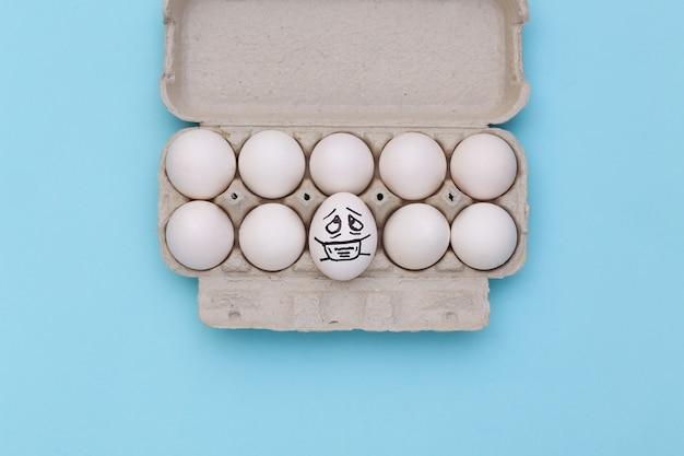 Cara de ovo em máscara médica na bandeja de ovos sobre fundo azul. pandemia do covid19. vista do topo