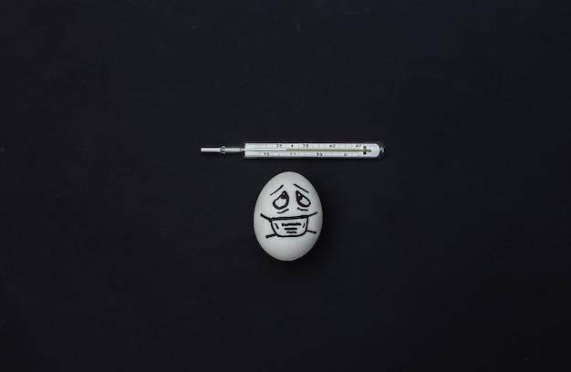 Cara de ovo em uma máscara médica e termômetro em fundo preto. pandemia do covid19. vista do topo