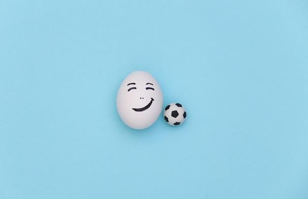 Cara de ovo feliz com bola de futebol em fundo azul