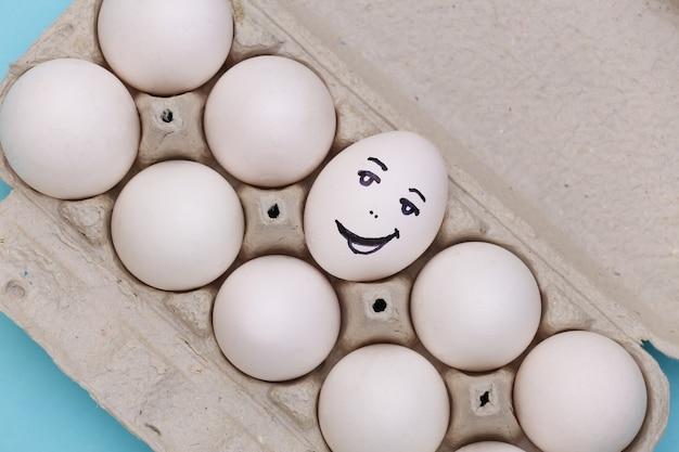 Cara de ovo feliz na bandeja de ovos sobre fundo azul. vista do topo