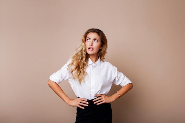 Cara de surpresa. mulher loira com roupa casual em cima de parede bege. menina saiu olhando.