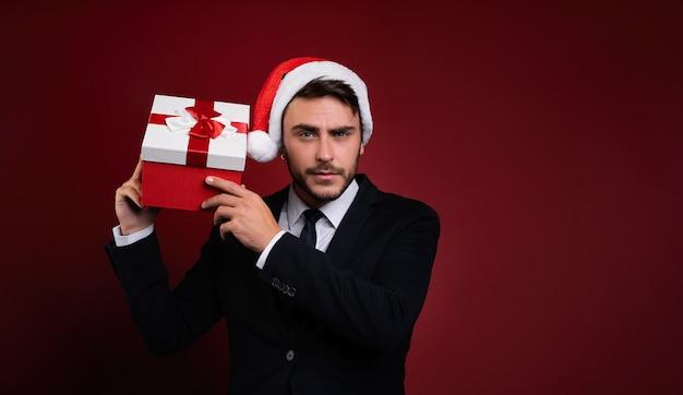 Cara de terno e chapéu de papai noel com presente de natal