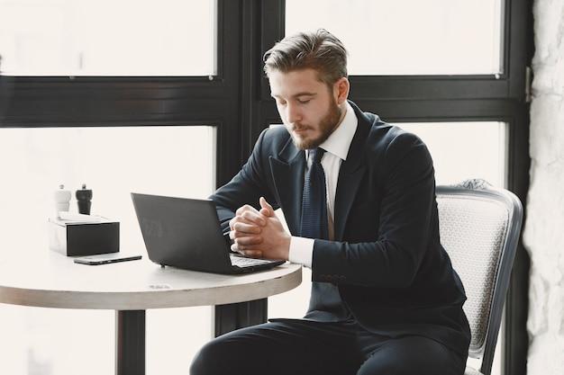 Cara de terno preto. macho no restaurante. homem com computador.