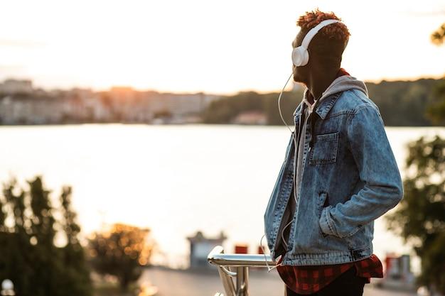 Cara de tiro médio com fones de ouvido e jaqueta jeans