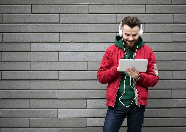Cara de tiro médio com fones de ouvido e tablet