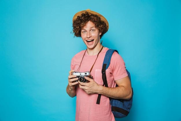 Cara de turista sorridente com cabelos cacheados, usando mochila e chapéu de palha fotografando na câmera retro