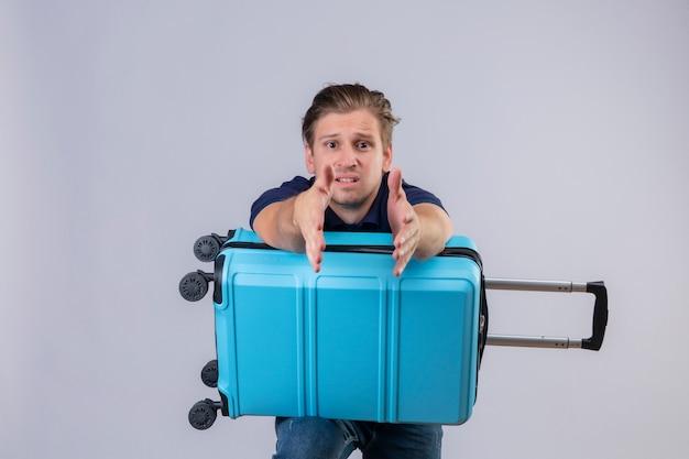 Cara decepcionado jovem viajante bonito em pé com mala esticando as mãos para fora olhando para a câmera pedindo ajuda sobre fundo branco