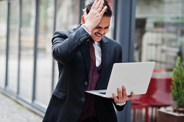 Cara desapontada do homem de negócios indiano à moda no vestuário formal com o portátil nas mãos que estão contra janelas no centro de negócios.