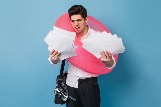 Cara descontente de camisa branca, segurando uma pilha de papel de escritório. morena masculina posando com anel de borracha rosa contra o espaço azul.