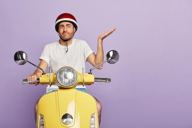 Cara desorientado e perplexo com capacete dirigindo uma scooter amarela