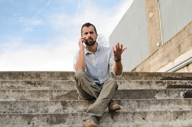 Cara discutindo e briga celular, sentado na escada rural da cidade. homem falando usando smar
