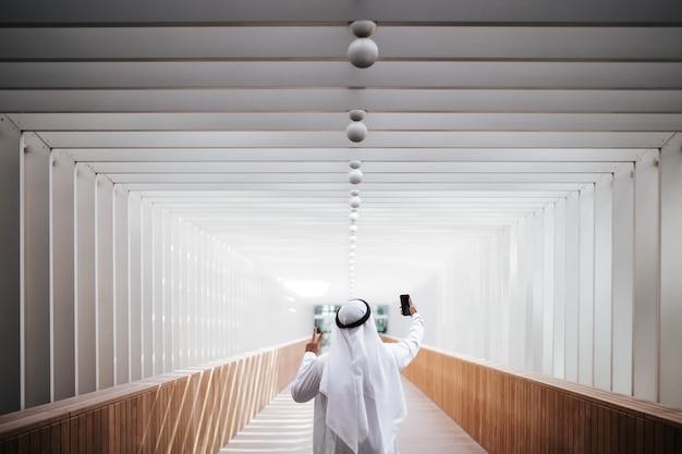 Cara do emirado tirando uma selfie no estilo de vida urbano de uma cidade no centro de dubai