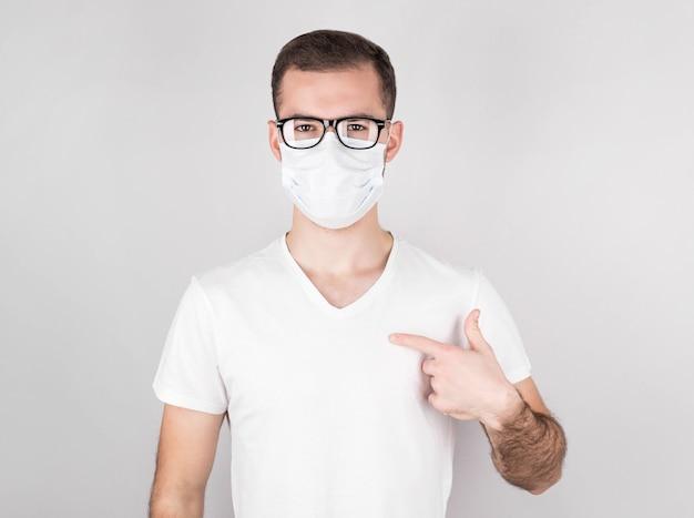 Cara do sexo masculino jovem em t-shirt casual posando isolado no retrato de parede cinza. conceito de estilo de vida de emoções de pessoas. copie o espaço para a cópia. apontando com o dedo indicador para a máscara branca