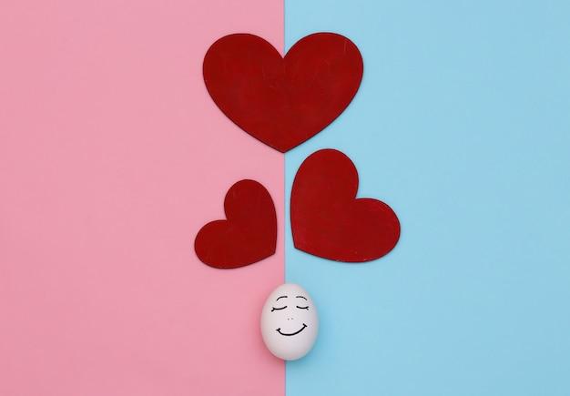 Cara e coração de ovo apaixonados em um fundo pastel rosa-azulado. dia dos namorados. vista do topo
