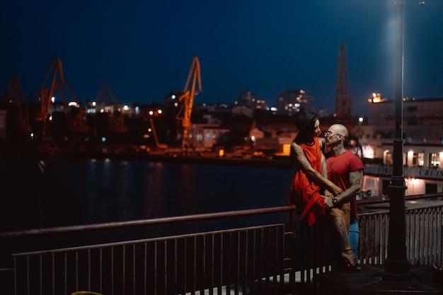 Cara e menina, abraçando-se em um fundo do porto noturno