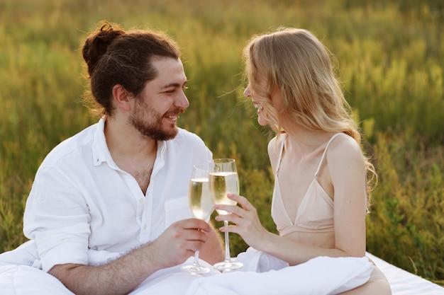 Cara e menina loira bebem champanhe de óculos e sorriem no parque à noite ao pôr do sol