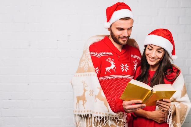 Cara e mulher em chapéus de festa, lendo o livro