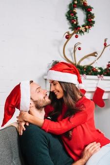 Cara e mulher em chapéus de Natal abraçando no sofá