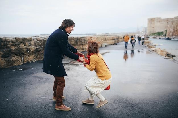 Cara e mulher se divertem na rua na chuva