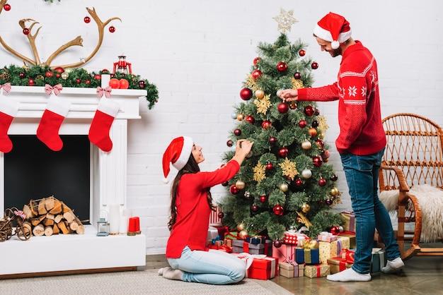 Cara e mulher vestindo árvore de natal com enfeites
