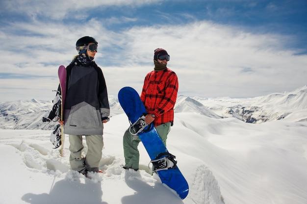 Cara e uma garota em roupas quentes ficar com pranchas de snowboard contra os topos de neve da montanha