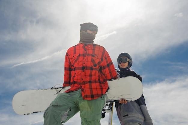 Cara e uma garota ficar na neve com pranchas de snowboard nas mãos contra o céu azul