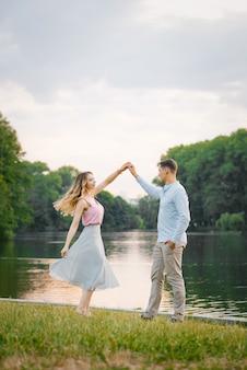 Cara elegante e romântica e garota dançando no lago em uma noite de verão