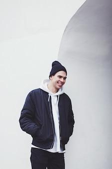 Cara elegante e sorridente usando um gorro preto e uma jaqueta de inverno perto de uma parede branca