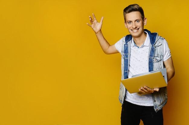Cara elegante hipster com roupa casual, posando com um laptop em uma parede amarela, isolada.