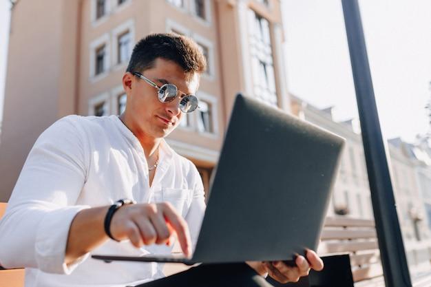 Cara elegante jovem de camisa com telefone e notebook no banco ensolarado dia quente ao ar livre, freelance