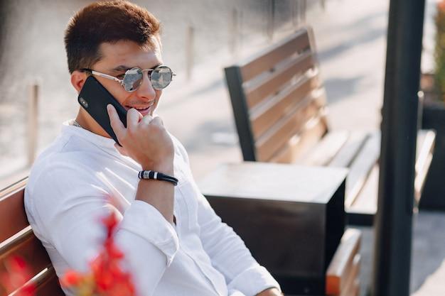 Cara elegante jovem de camisa com telefone no banco em telefonemas ensolaradas de dia quente ao ar livre
