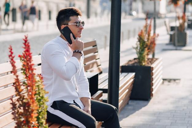 Cara elegante jovem de camisa com telefone no banco ensolarado dia quente ao ar livre