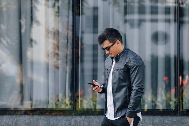 Cara elegante jovem de óculos na jaqueta de couro preta com telefone na superfície de vidro