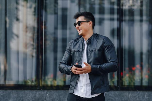 Cara elegante jovem de óculos na jaqueta de couro preta com telefone